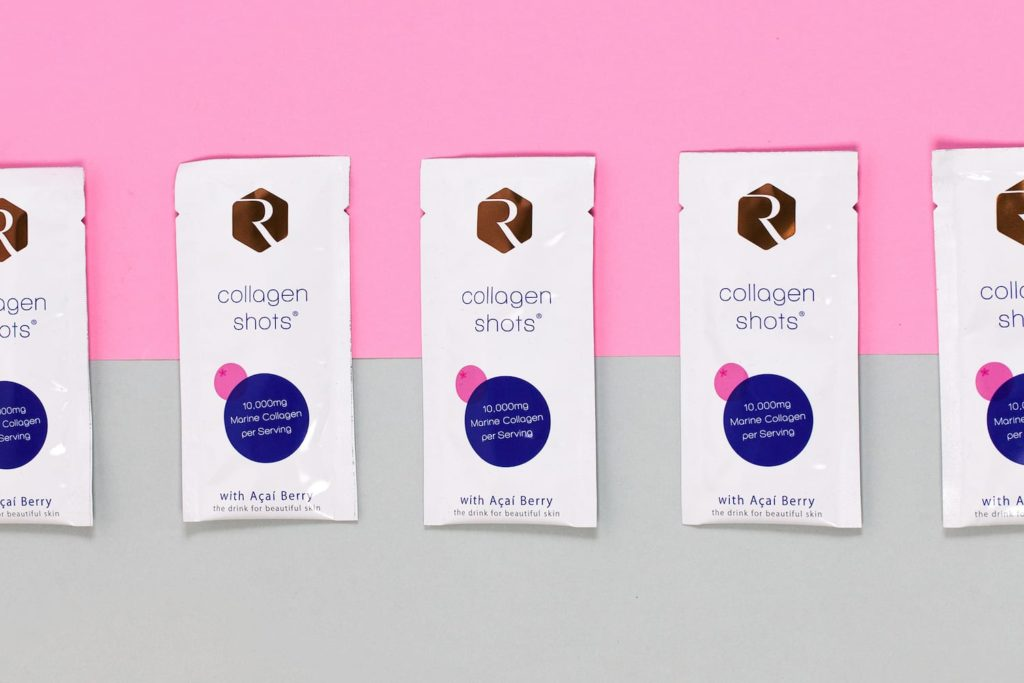 Collagen Shots sachets on pink and grey background